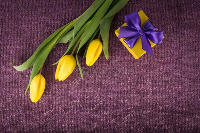 Tulipes et boîte-cadeau jaunes sur le fond tricoté violet photos libres de droits