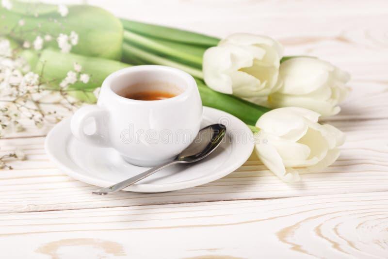 Tulipes et café de ressort sur un plan rapproché en bois blanc de fond Fond du jour de mère, le jour des femmes, anniversaire de  images stock