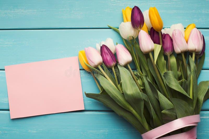 Tulipes et carte de voeux colorées s sur le fond bleu, l'espace de copie photos libres de droits
