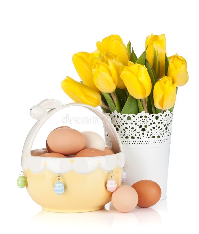 Tulipes et oeufs jaunes frais dans la cuvette images stock