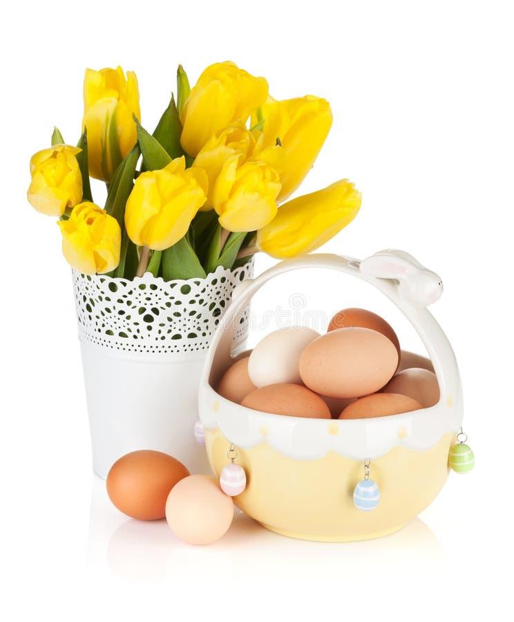 Tulipes et oeufs jaunes frais dans la cuvette photographie stock