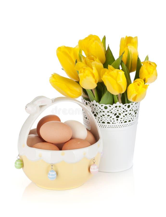 Tulipes et oeufs jaunes frais dans la cuvette image stock