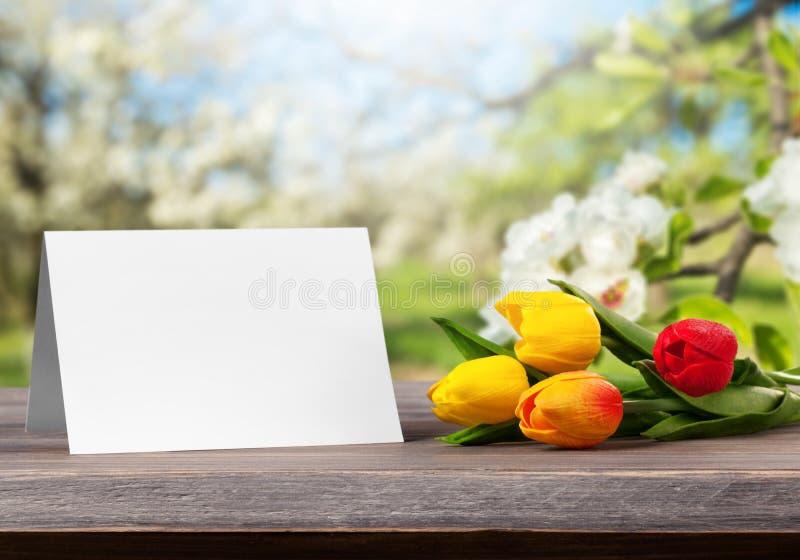 Tulipes fraîches avec la carte vierge sur la table en bois image stock