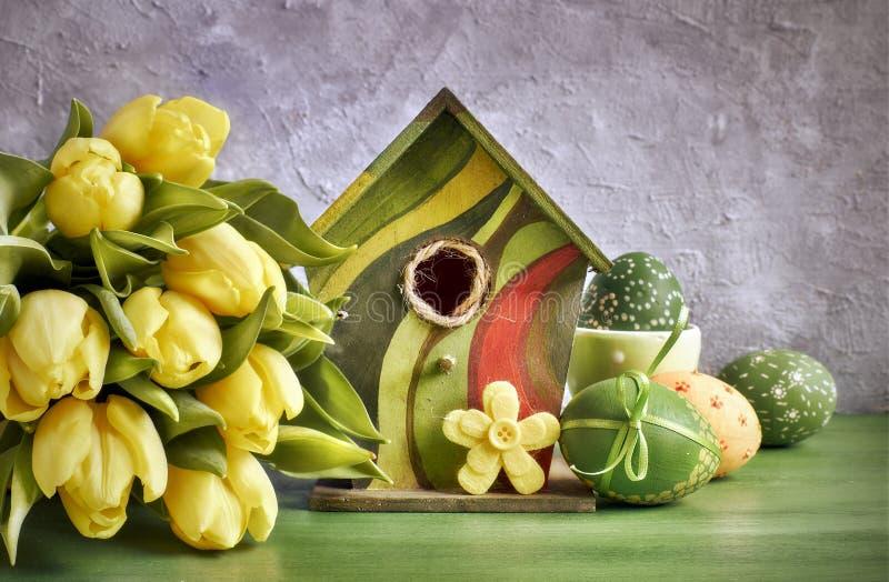 Tulipes jaunes, volière et oeufs de pâques peints avec décoratif photo stock