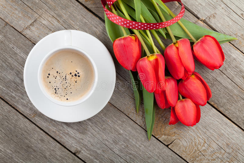 Tulipes rouges fraîches avec la tasse de ruban et de café image libre de droits
