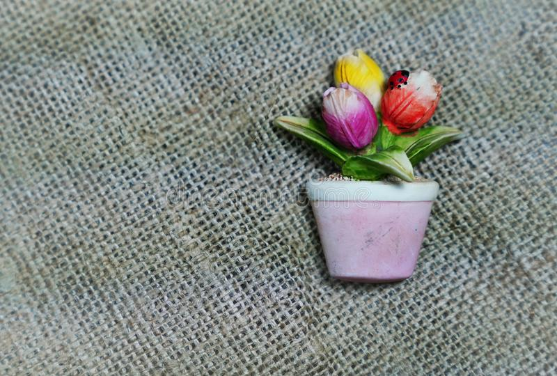 Tulips flower in vase as magnetic souvenir on sackcloth stock photos