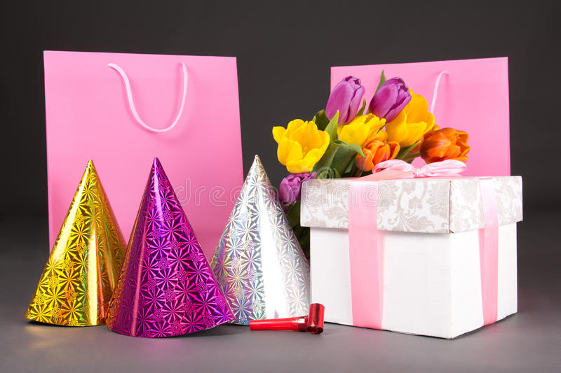 Tulips, gift boxes and birtday hats. On grey stock image