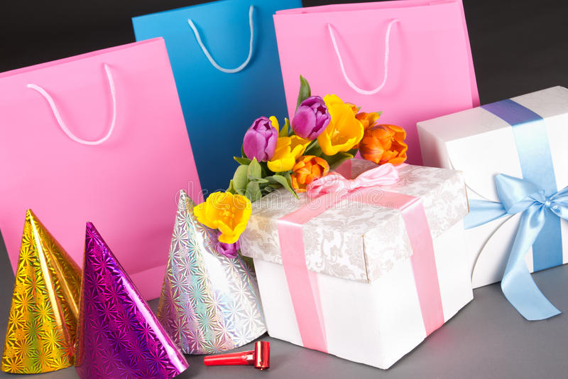 Tulips, gift boxes and birtday hats over grey. Composition of tulips, gift boxes and birtday hats on grey stock photos