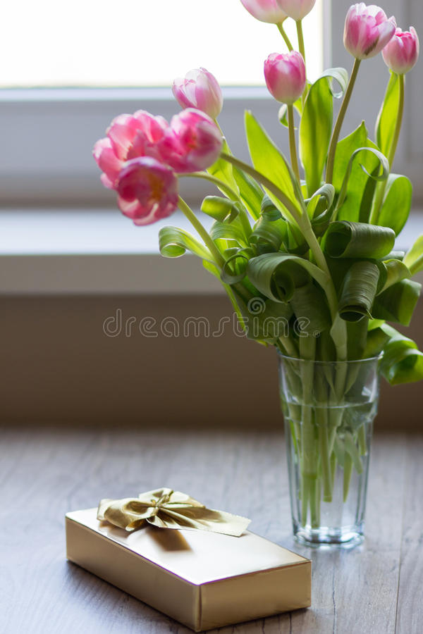 Tulips and gift on a gray background. Tulips and gift on gray wooden background royalty free stock photo