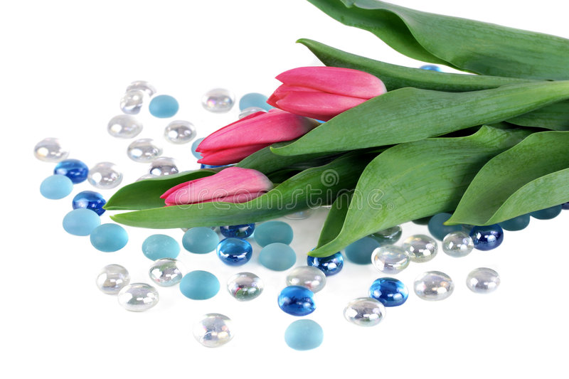 Tulips laying on white table with glass beads stock photography