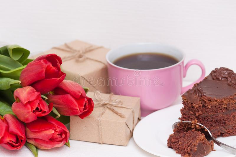 Tulips, presents, cake, cup for mother, wife, daughter, girl. Happy birthday, Mother`s day. Woman`s day stock image