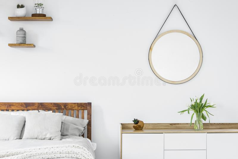 Tulips on a scandinavian style dresser, wooden shelves with plan. Ts and a vase and round mirror in a white bedroom interior stock images