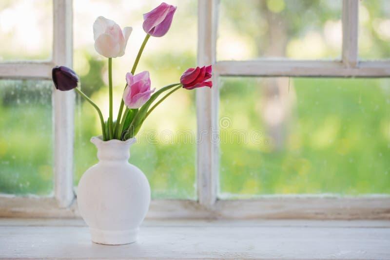 Tulips in vase on old windowsill. Pink tulips in vase on old windowsill royalty free stock image