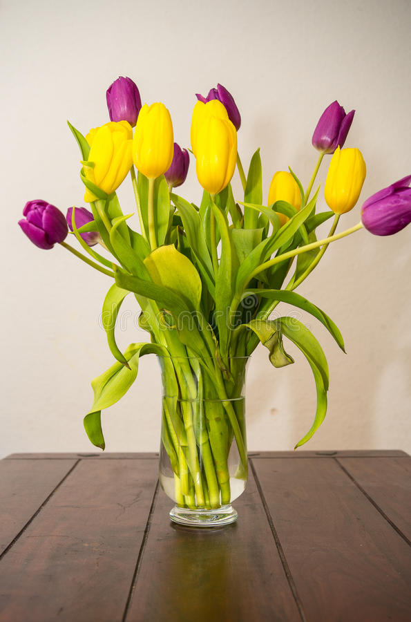 Tulips in a vase. On a table royalty free stock photos