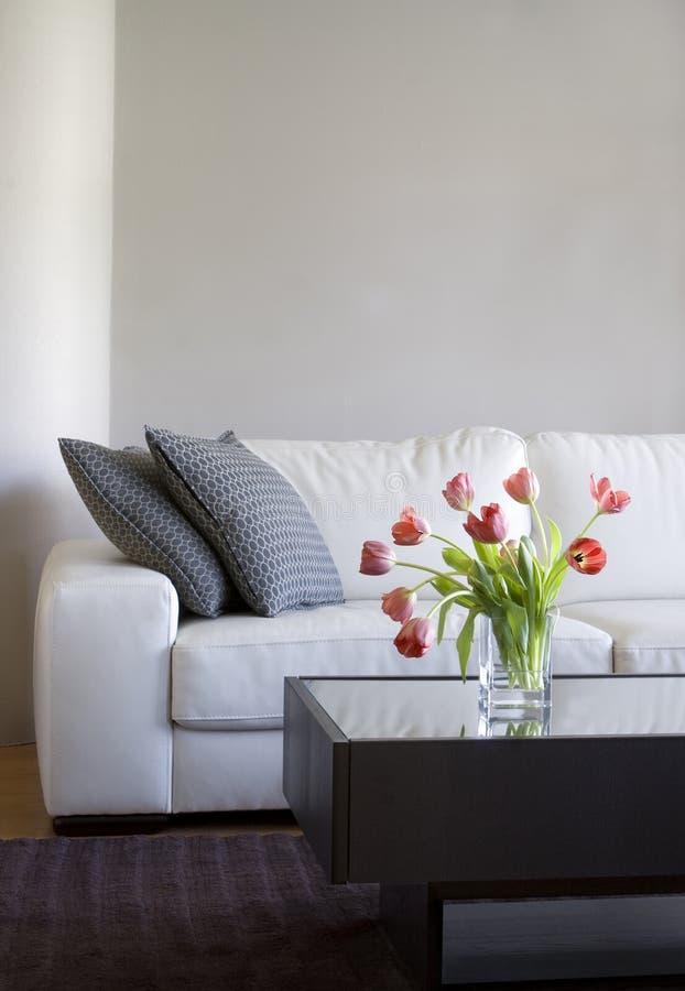 Tulips vermelhos na sala de visitas moderna - decoração home fotografia de stock royalty free