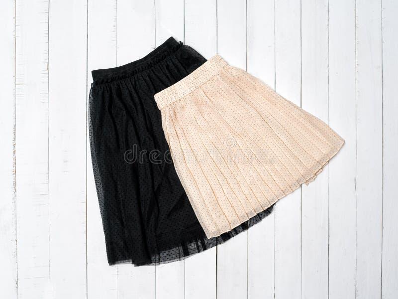 Tulle negra y falda beige en el fondo de madera blanco Visi?n superior fotos de archivo libres de regalías