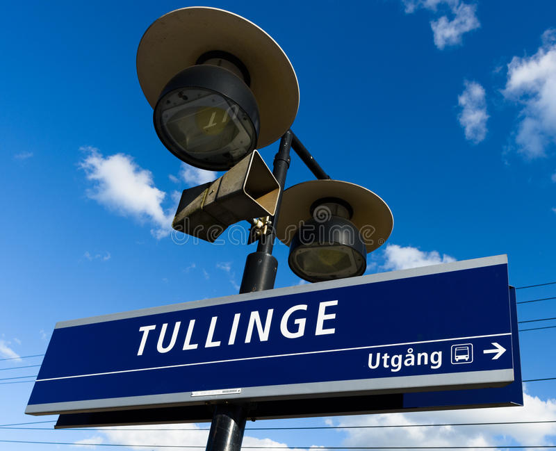 Tullinge train station with the station sign. Tullinge, Sweden - August 12, 2015: Tullinge train station with the station sign, speaker, sign show exit direction royalty free stock photo