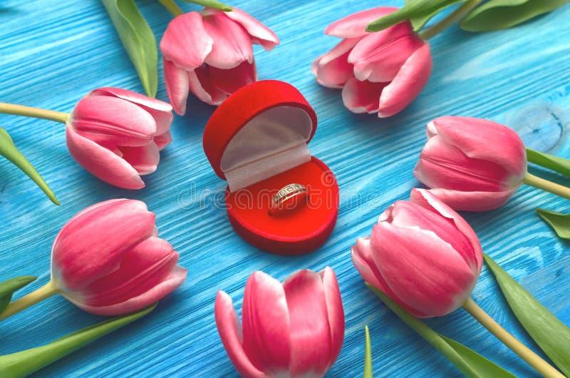Tulpan blommar och vigselringen i en gåvagåvaask på träbakgrund Förbindelseerbjudande Förslaget royaltyfri foto