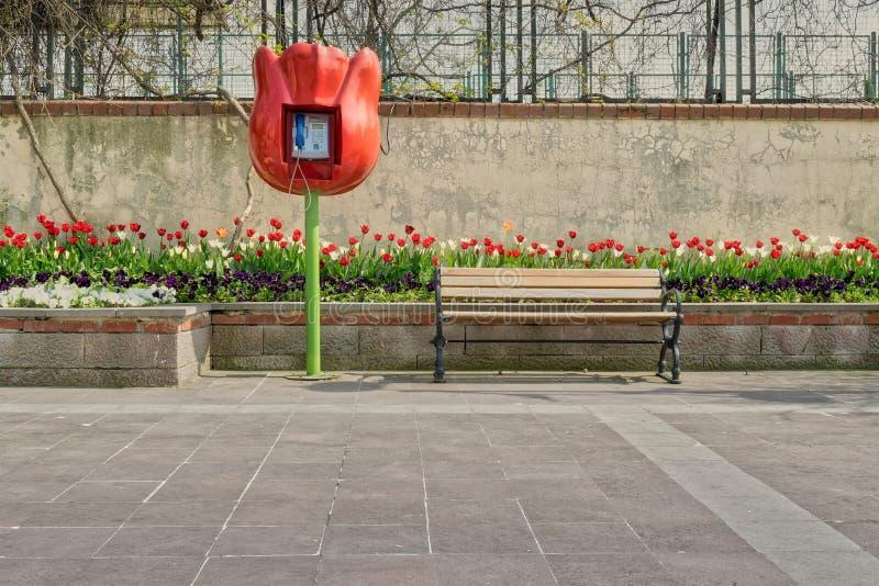 Tulpan formad offentlig telefon och träbänk framme av den inbyggde tulpanblommaasken och grungeväggen på belagt med tegel stengol royaltyfri bild