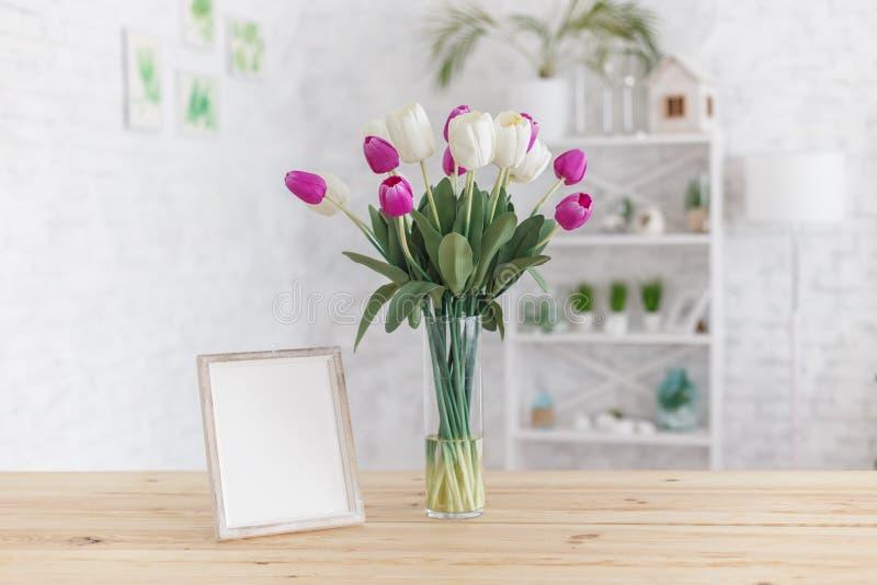 Tulpan i en vas på en trätabell inre scandinavian Modell arkivbild