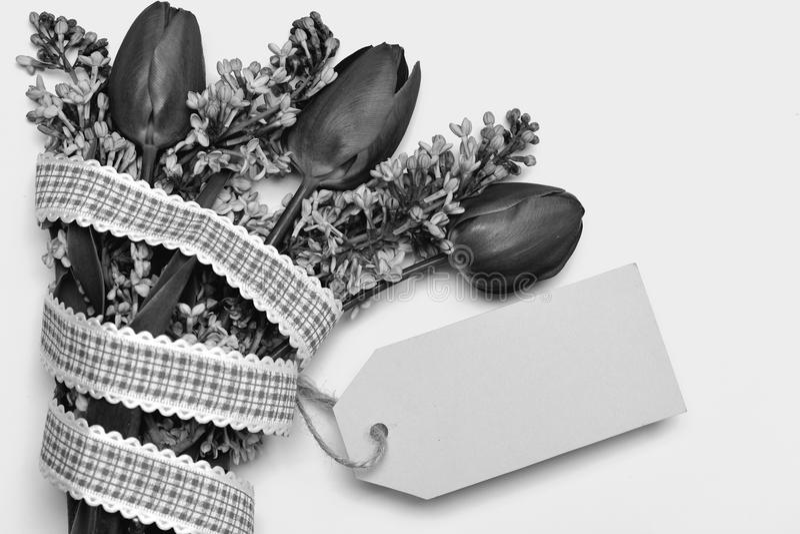 Tulpan- och lilablommor med bandet och den cyan anmärkningsetiketten royaltyfri foto