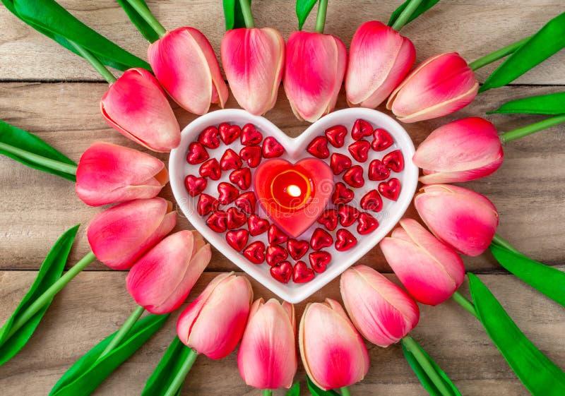 Tulpanblommor läggas ut i formen av en hjärta på en träbakgrund, bland dem är enformad platta och en brinnande hjärta royaltyfri bild
