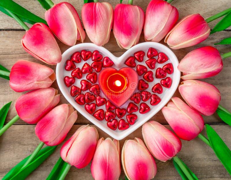 Tulpanblommor läggas ut i formen av en hjärta på en träbakgrund, bland dem är enformad platta och en brinnande hjärta royaltyfri foto