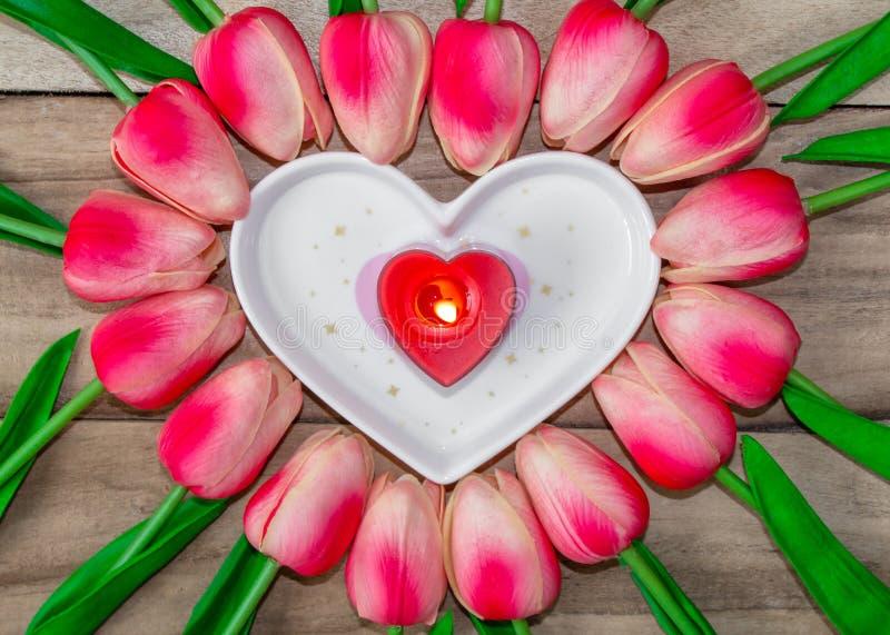 Tulpanblommor läggas ut i formen av en hjärta på en träbakgrund, bland dem finns det enformad platta och en inscrip arkivbild