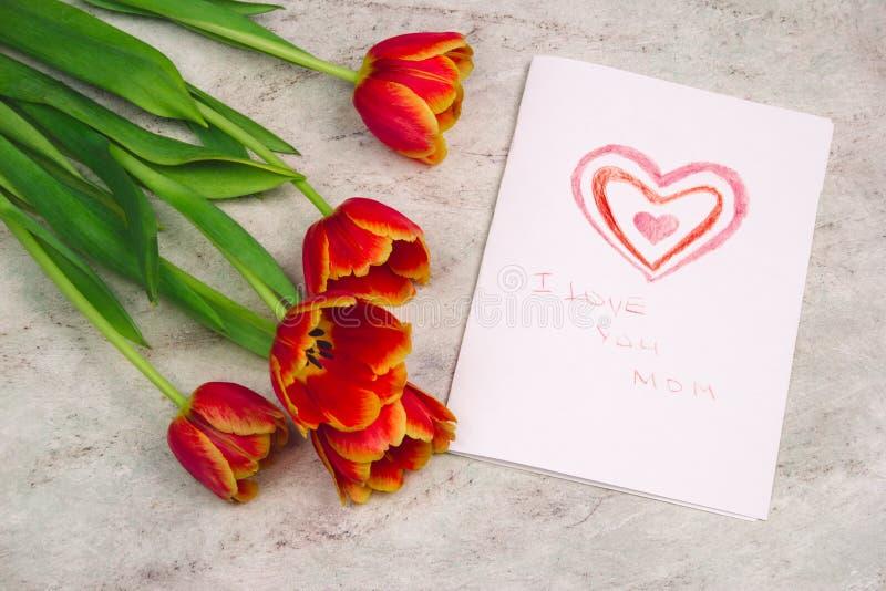 Tulpen en met de hand gemaakte kaart met de tekening van het jonge geitje voor Moederdag op marmeren achtergrond, hoogste mening royalty-vrije stock afbeelding