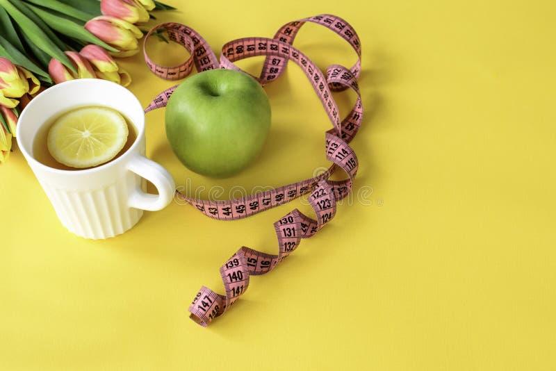 Tulpen, groene appel, kop van aftreksel met citroen en meetlint op gele achtergrond Concept de lente detox stock foto