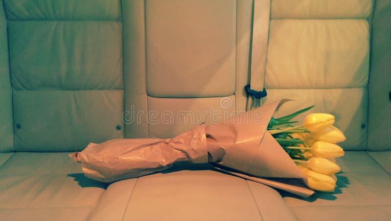 Tulpen im braunen Papier auf Autositz stockfotografie