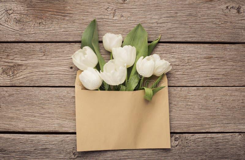 Tulpenblumenstrauß im Umschlag, Frühlingsfeiertagskonzept lizenzfreie stockbilder