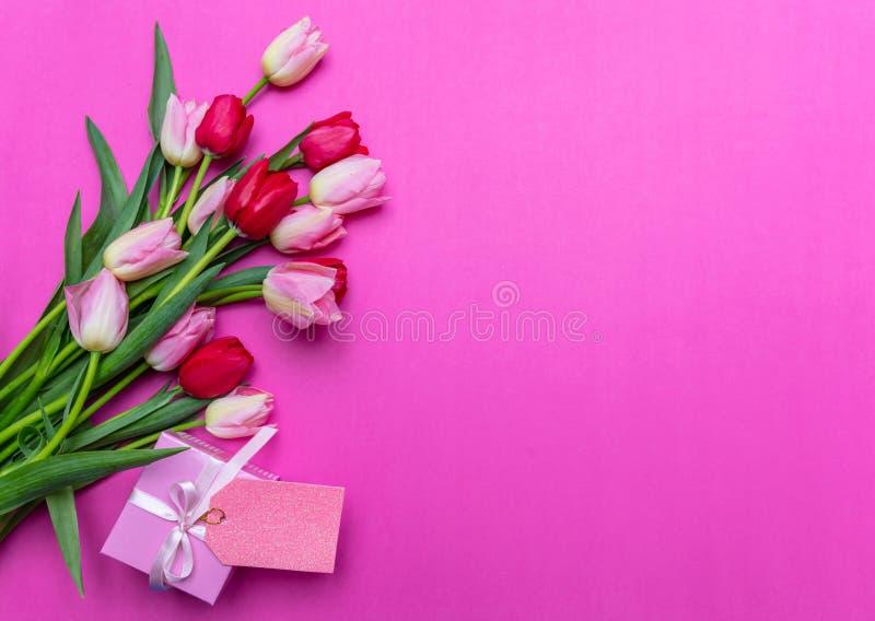 Tulpenboeket en giftvakje met lege markering op heldere roze achtergrond, hoogste mening, exemplaarruimte royalty-vrije stock foto's