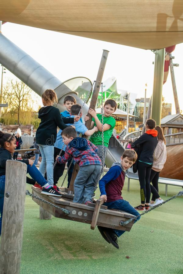 Tulsa OK Diverse group of children playing of a boat swing at the Gathering Place - Award Winning Public Park in Tulsa royalty free stock image