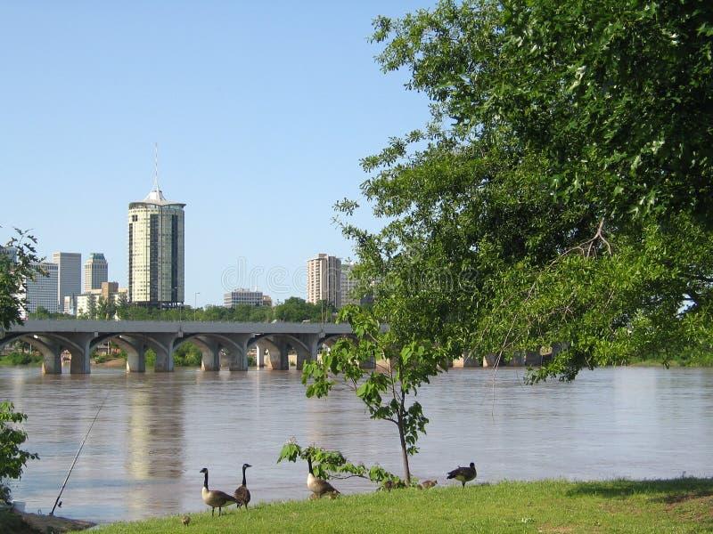 Tulsa Oklahoma från den västra banken av Arkansaset River med behandla som ett barn gäss och en fiskepol royaltyfri foto