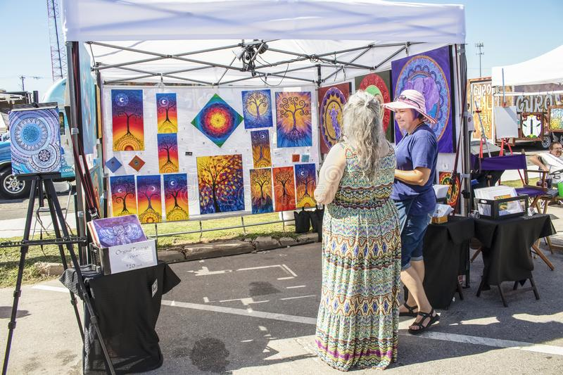 Art booth at city festival - artist and customer discuss artwork stock photos