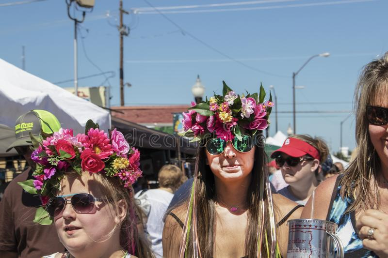 Girls at festival wearing flower crowns with streamers walking in street among crowd - close-up and selective royalty free stock image