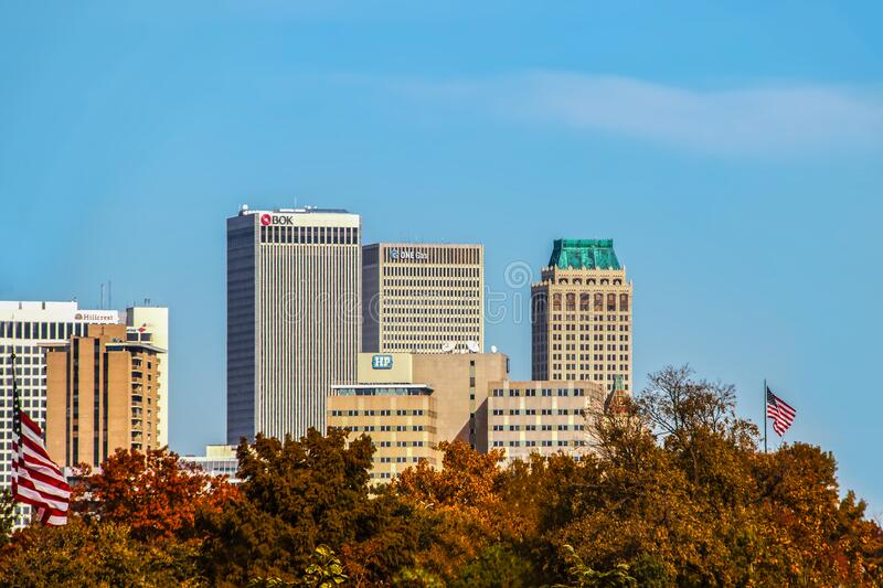 Tulsa USA Skyline of Tulsa OK - wit modern and Art Deco buildings - viewed over fall trees with American flags waving in. 11-7-2020 Tulsa USA Skyline of Tulsa OK royalty free stock image