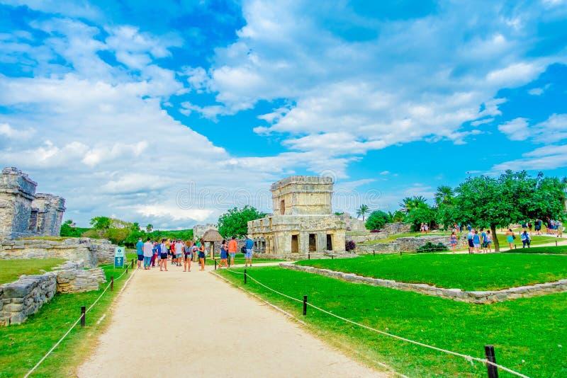 TULUM, MÉXICO - 10 DE JANEIRO DE 2018: Turistas não identificados que andam e que apreciam a vista do templo dos fresco no fotografia de stock