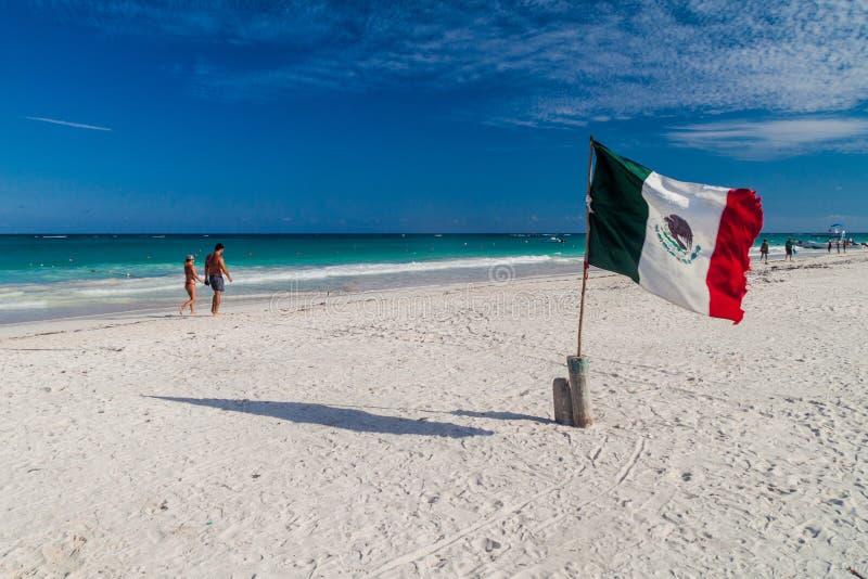 TULUM, MEXIO - FEB 29, 2016: Mexican flag at the Caribbean beach in Tulum, Mexi. Co royalty free stock photos