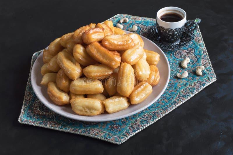 Tulumba - arabian syrup-soaked fried sponge honey with cup of coffee on black background. Arabic sweets celebration Eid Ramadan.  royalty free stock photography