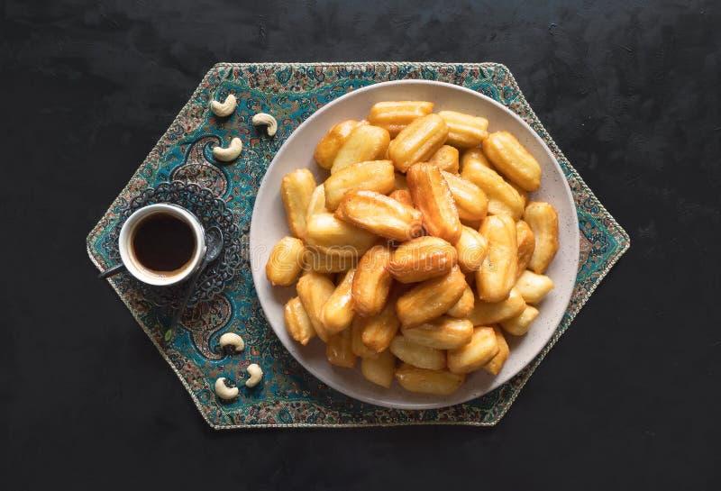 Tulumba - arabian syrup-soaked fried sponge honey with cup of coffee on black background. Arabic sweets celebration Eid Ramadan.  royalty free stock image