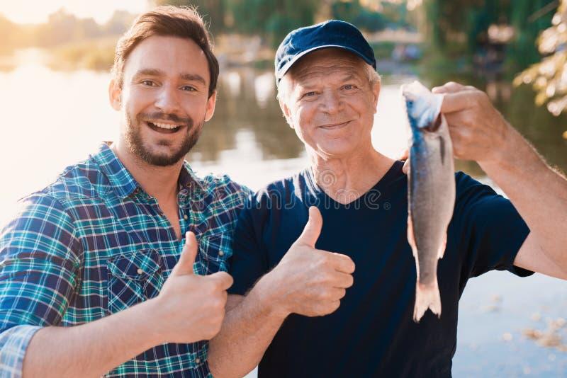 tum upp En man står bredvid en gamal man som rymmer en fisk som, han har precis fångat royaltyfri fotografi