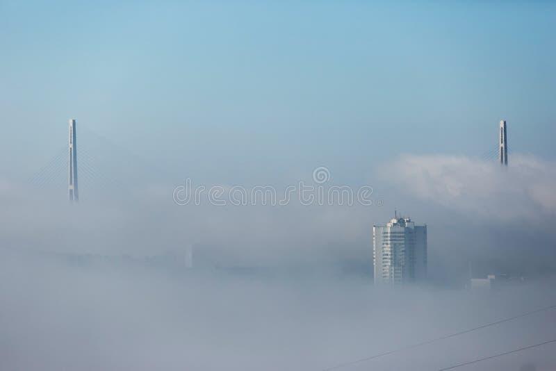 Tuman在符拉迪沃斯托克  在雾掩藏的俄国和金黄桥梁的定向塔 图库摄影