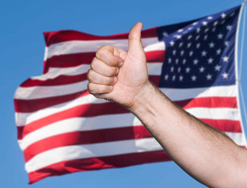 Tumb up sign against of USA flag. Patriotic concept. Tumb up sign against of United States of America flag stock photography