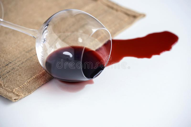 Tumbled glass goblet on the table from it pours out red wine, the concept. Tumbled glass goblet on the table from it pours out red wine, the concept royalty free stock image