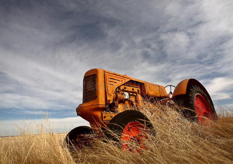 Tumbleweeds piled against abandoned tractor. Saskatchewan Canada Prairie royalty free stock images