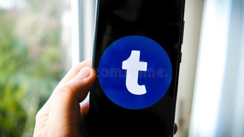 Tumblr app på smartphonehanden fotografering för bildbyråer