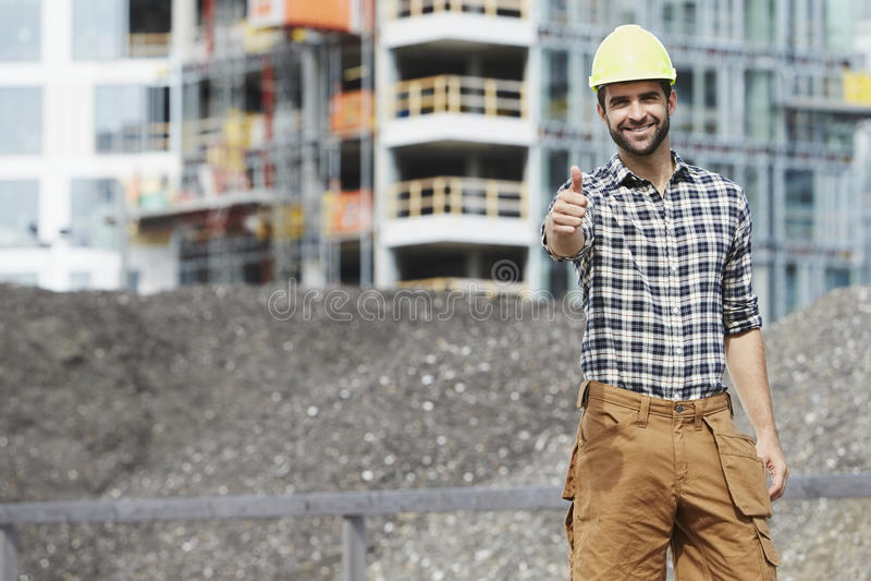 Tummar up byggnadsarbetaren arkivfoto
