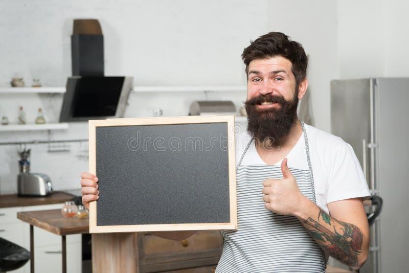Tummar upp för bästa skola Lycklig skäggig man som rymmer den tomma svart tavla i skola Hipsterkock som undervisar i kulinariskt royaltyfri fotografi